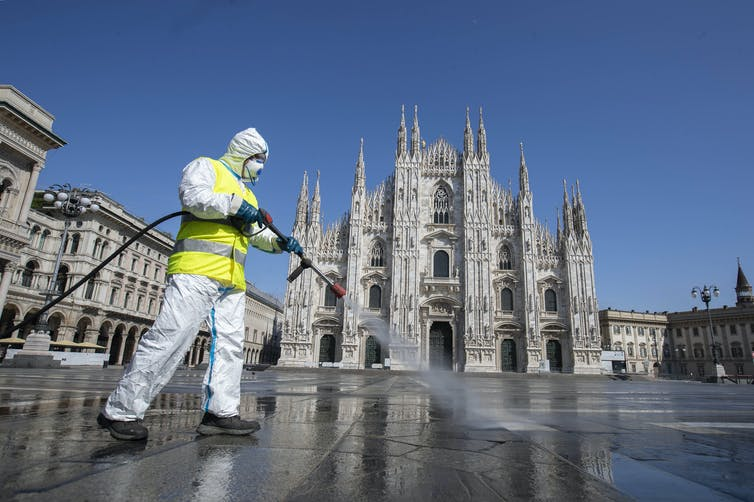 Cleaner in hazmat suit disinfecting the pavement in Duomo square, Milan, Italy.