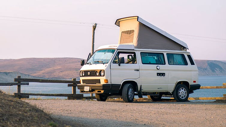 A campervan parked up with the roof extended.