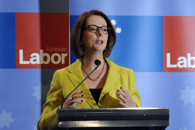 Julia Gillard in front of a Labor sign