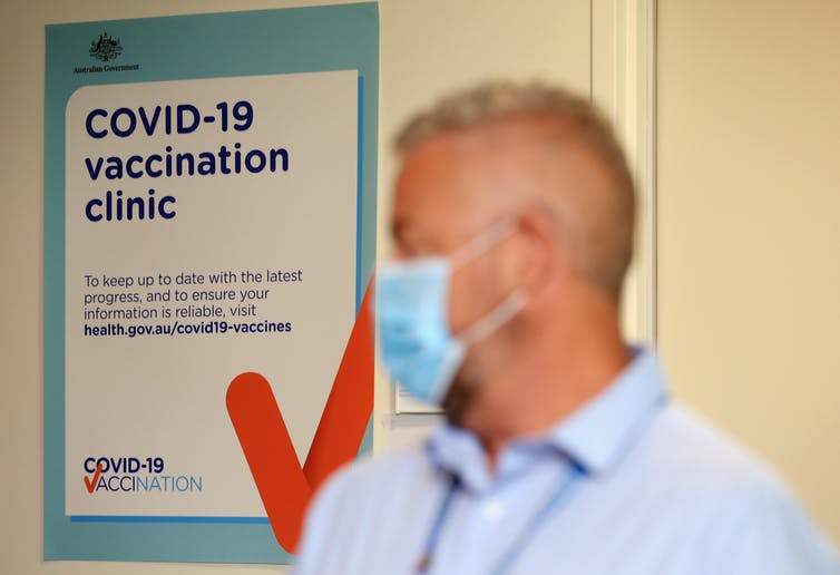 A man wearing a mask walks past a sign saying 'COVID-19 vaccination clinic'.