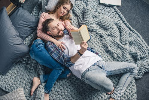 Man laying on woman's chest on the floor on top of a blanket while reading to her
