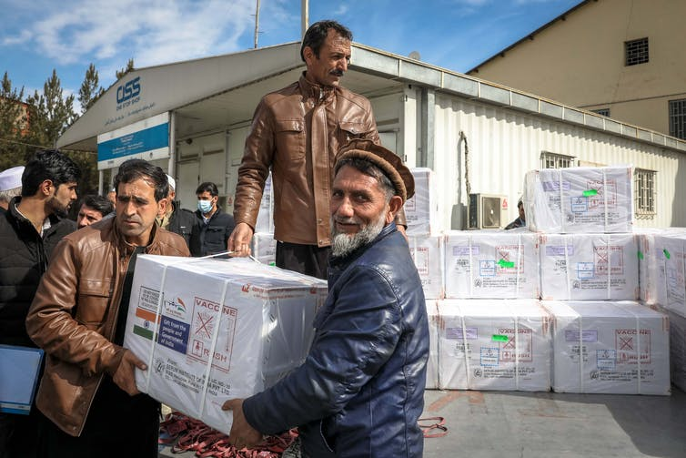 Men loading cartons of AstraZeneca vaccines on to a lorry at Kabul airport in Afghanistan, February 2021.