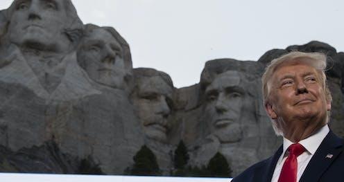 Trump smiles at Mount Rushmore.