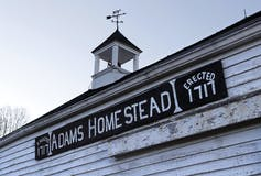 A sign on a white clapboard carriage house reads Adams Homestead, Erected 1717
