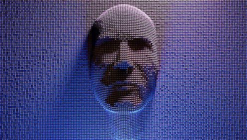 A man's face pushes through ball bearings