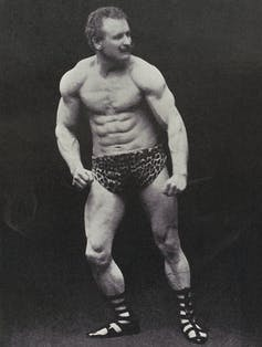 Eugen Sandow wearing leopard-skin trunks and Classical-style sandals.