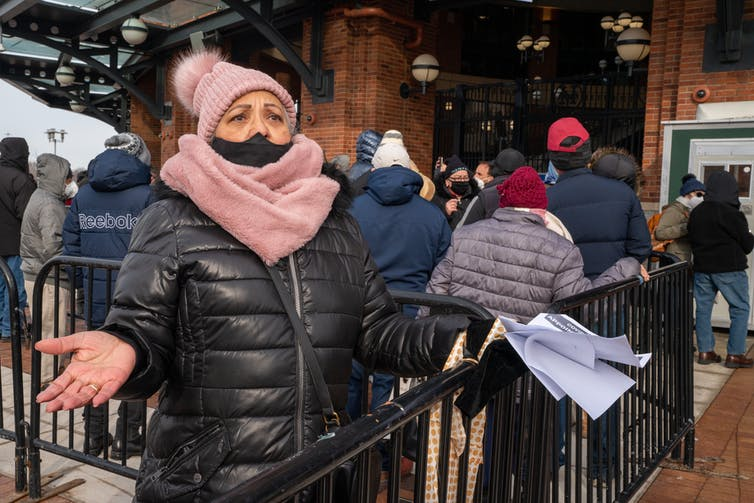 A woman holds up paperwork in frustration outside a stadium vaccine site