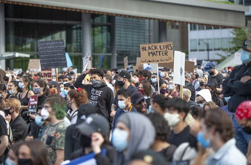 Protesters carry Black Lives Matter placards
