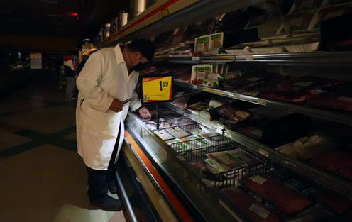 A man uses light from a cell phone to arrange products in the meat section of a grocery store.