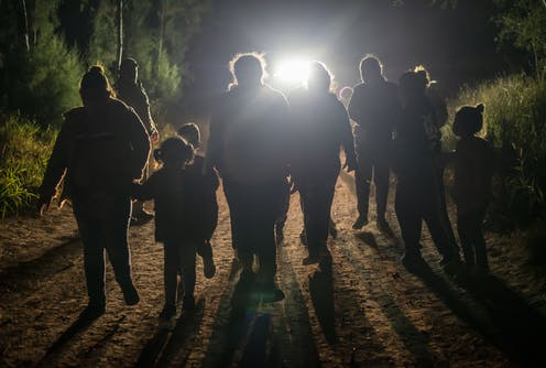 A group of people -- adults and children -- after being apprehended trying to cross into the US near Mission, Texas.