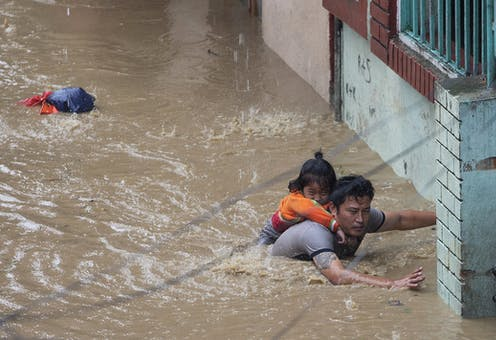 Man carries child through floodwaters in Nepal