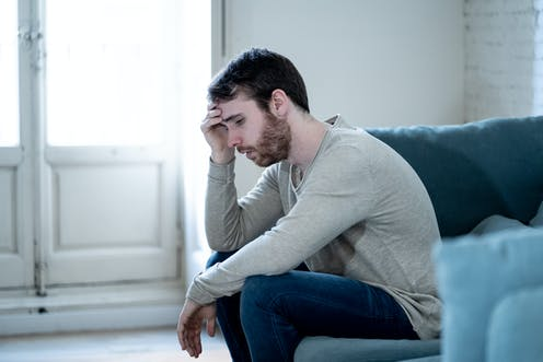 A young man sits on a couch looking sad.