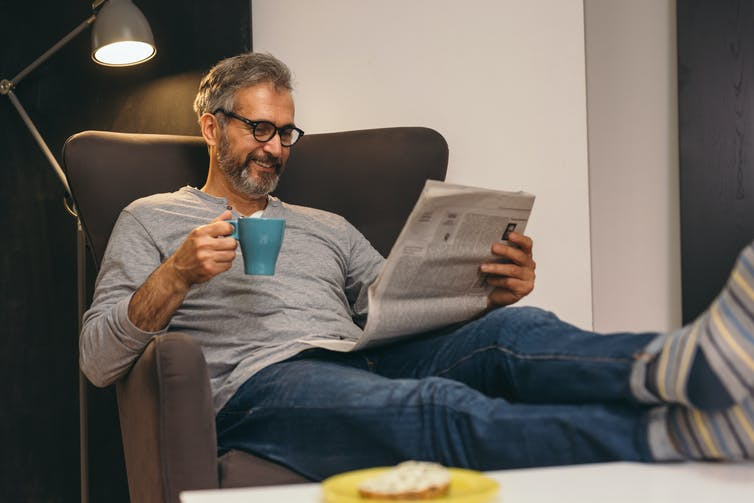 A man sits on the couch reading a newspaper, with a mug in hand.