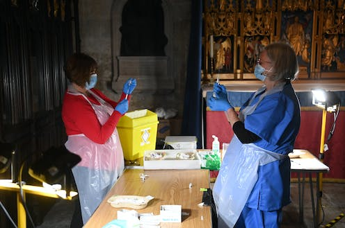Two clinicians dose up syringes with COVID vaccines in Salisbury Cathedral, where a vaccination centre as has been set up.