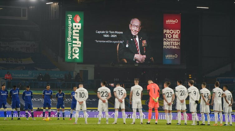 Football players stand in front of screen with tribute to Captain Tom Moore