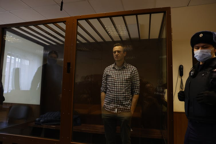 Alexei Navalny standing in court in a glass cell.