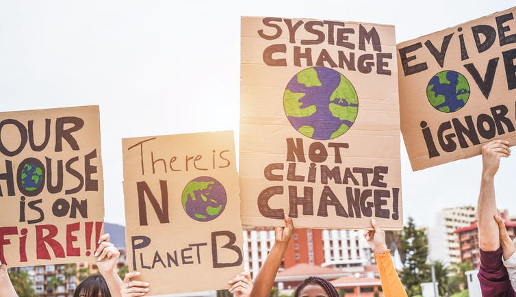Climate activists carrying signs demanding action.