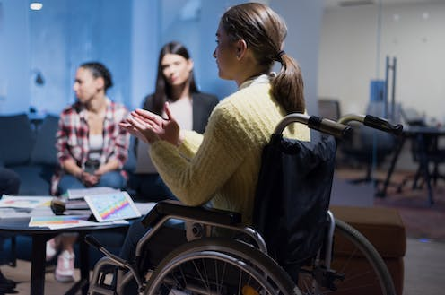 Woman in wheelchair talks to colleagues during a meeting