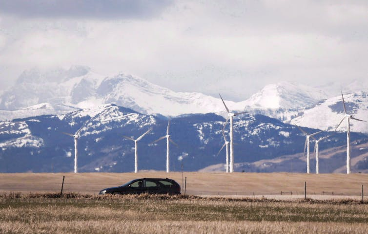 A car driving past several wind turbines with mountains in the background.