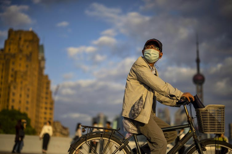 A man wearing a COVID mask rides a bicycle in with a cityscape behind him.
