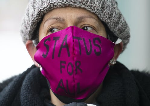 """A woman wears a pink mask which says, """"Status for all."""""""