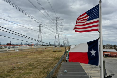 Texas and US flags fly near transmissions linees.