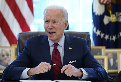 Joe Biden sits at his desk in the Oval Office holding a pen in front of a folder with papers