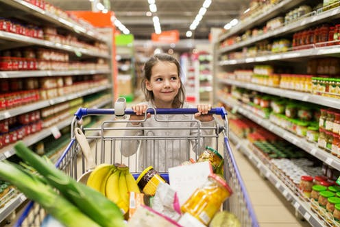Girl with shopping trolley in supermarket.