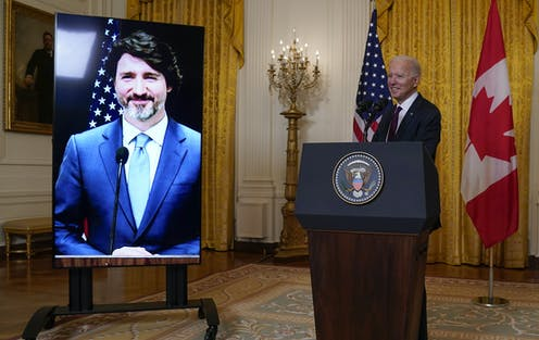 Biden stands behind a podium as Trudeau smiles on a screen.