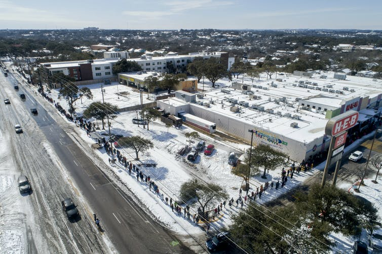 Aerial view of a long line to buy groceries in the snow