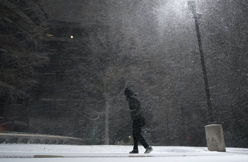 A person dressed in black walks through a blizzard at night