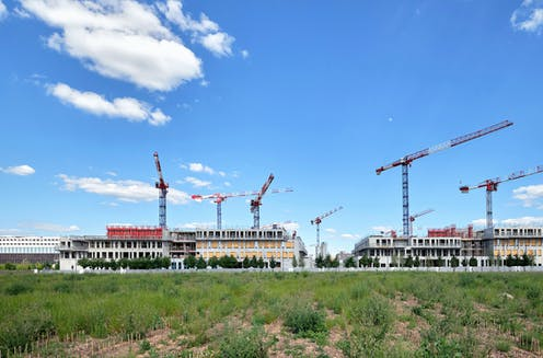 cranes tower over a large campus under construction