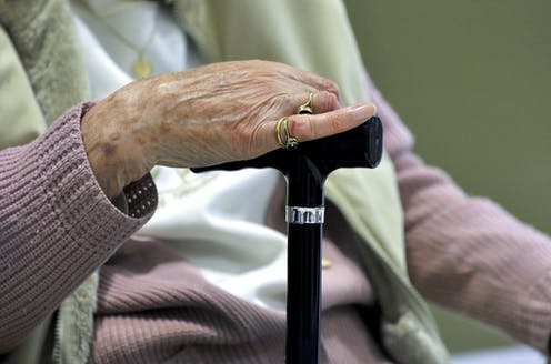 Older person's hand resting on a walking cane