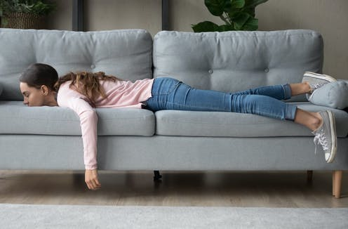 A girl lying on a sofa with her arm hanging down.