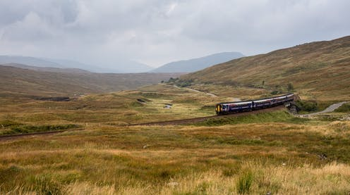 A three-carriage ScotRail train trundling across a bleak Rannoch Moor in the Highlands.