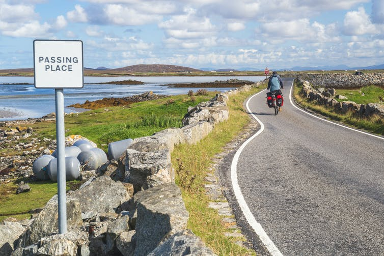A cyclist crossing one of the causeways on Uist on a blue-sky sunny day.