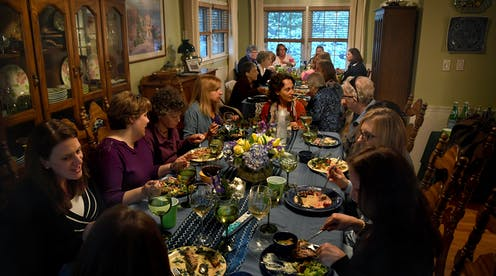 Large group of women converse and eat a shared meal at two dining room tables.