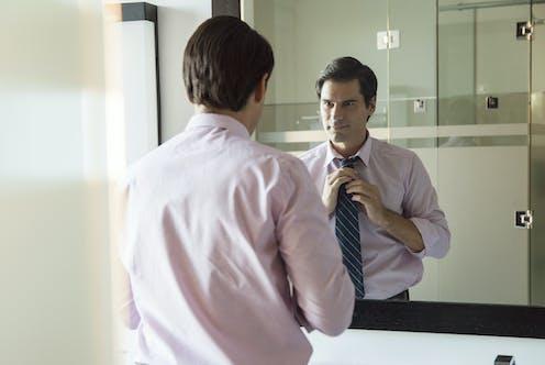 Man adjusting his tie in the mirror.