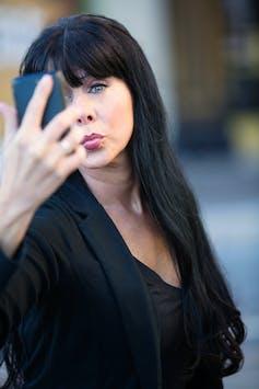 Eine Frau kräuselt ihre Lippen, während sie ein Selfie macht.