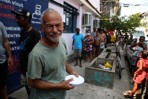 A man smiles after receiving a meal from a food bank in Rio de Janeiro, Brazil, October 2020.