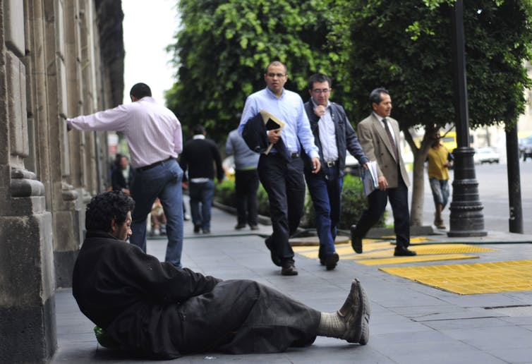 A man sits barefoot on the pavement in Mexico City begging as well dressed people walk past.