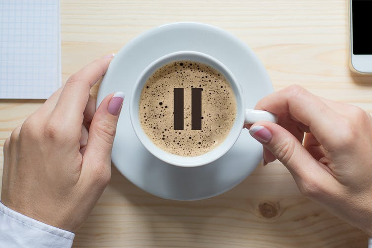 Overhead view of a cup of coffee with a 'pause' symbol in centre.
