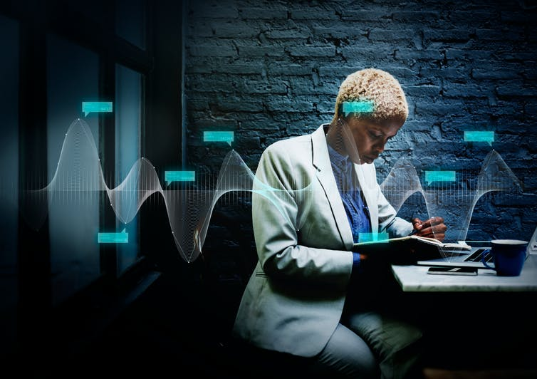 Black professional woman working on a laptop in a darkened office space with a curve graph overlaying the photo.