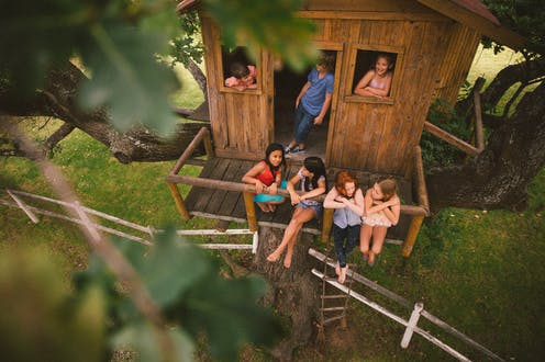 boys and girls playing and talking together in a rustic wooden treehouse, seen through the lush green leaves of a tree