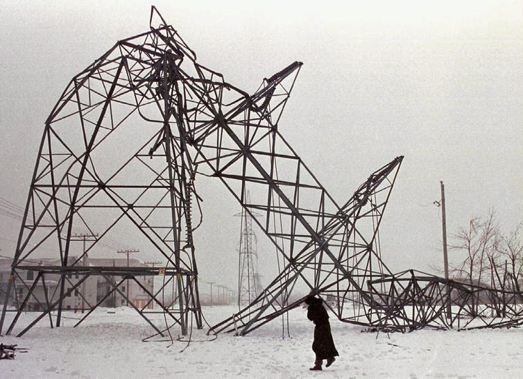 A transmission tower crumpled under the weight of ice.