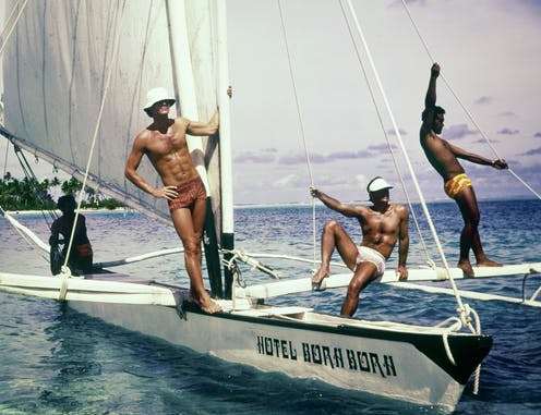 Three models pose on a sailboat wearing swim trunks.
