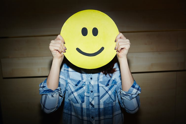 A woman holding a smiley face in front of her head.