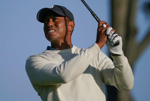 Tiger Woods holding golf club in air