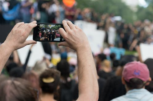 Man in crowd filming with smartphone