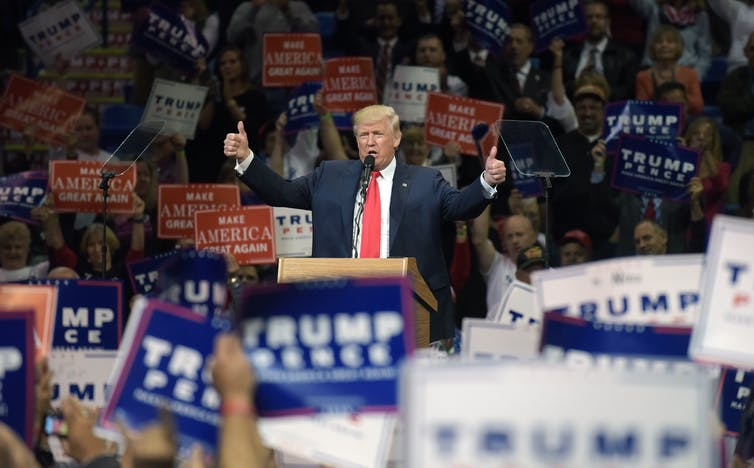 Donald Trump at a rally with crowds and placards